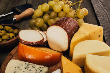Close up view of assortment of cheese on wooden cutting board and grapes stock vector
