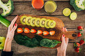 woman and cutting board with fresh vegetables and fruits