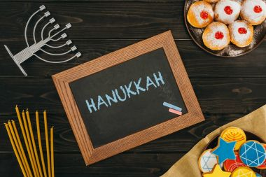 Top view of frame with hanukkah word, donuts and cookies with star of david on wooden tabletop stock vector
