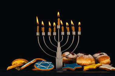 Traditional jewish menorah for hanukkah celebration, doughnuts and cookies,  isolated on black stock vector