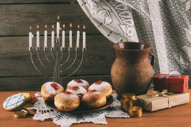 Traditional jewish menorah, ceramic jug, Hanukkah gelt, gifts and donuts for hanukkah celebration stock vector