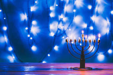 Traditional jewish menorah with candles with bokeh blue lights on background stock vector