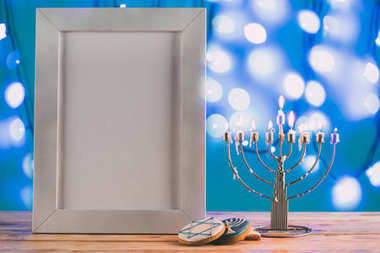 Frame with copy space, traditional hanukkah menorah and cookies with bokeh blue lights on background stock vector