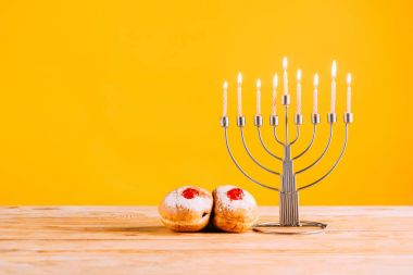 Hanukkah celebrating with menorah and donuts on wooden tabletop on yellow stock vector