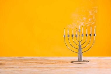 Menorah with candles standing on wooden tabletop on yellow, hanukkah celebrating stock vector