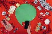 ruku s smartphone a vánoční řečovou bublinu