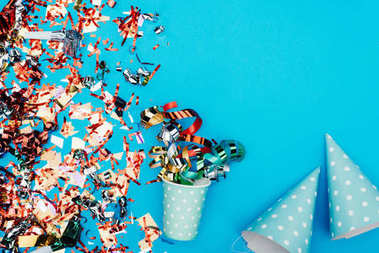 Top view of confetti with paper cup and party hats on blue tabletop stock vector