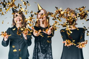 women throwing golden confetti
