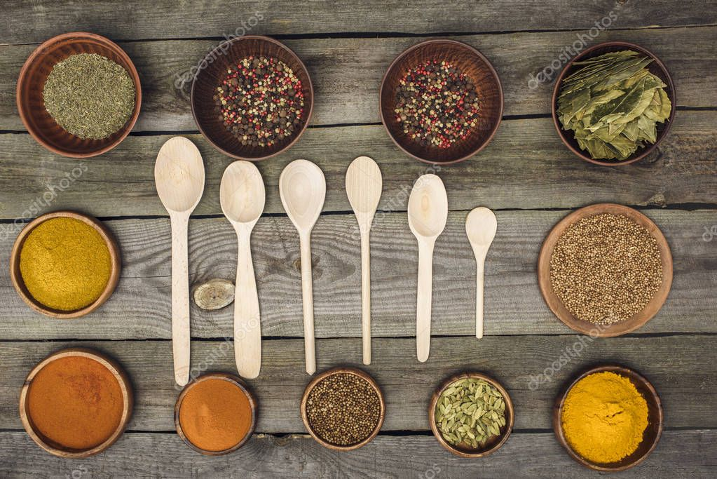 wooden spoons among bowls with spices