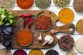 Photo bowls with spices on wooden board and table