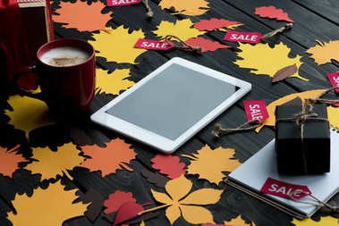 Top view of digital tablet, autumn leaves, coffee, presents and sale tags stock vector