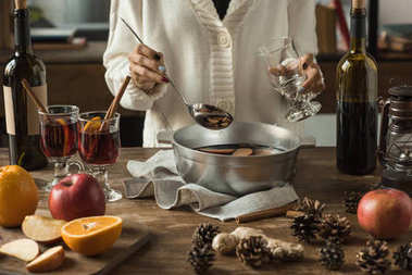 Cropped image of woman pouring homemade mulled wine stock vector