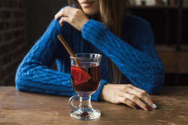 Cropped image of woman sitting at table with glass of mulled wine with cinnamon stick stock vector