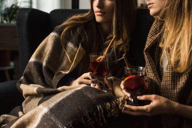 girls holding glasses of mulled wine