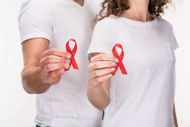 couple holding red aids ribbons