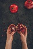 Fotografie žena držící kousky granátového jablka