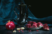 Fotografie Black teapot and pomegranates