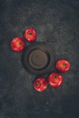 pomegranates around empty plate