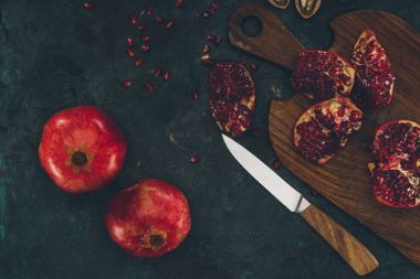 knife and pomegranate on wooden board