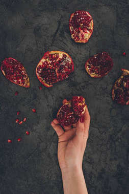 woman holding pomegranate piece in hand