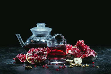 Glass and teapot with pomegranate juice