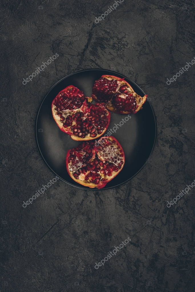 cut pomegranate on black plate