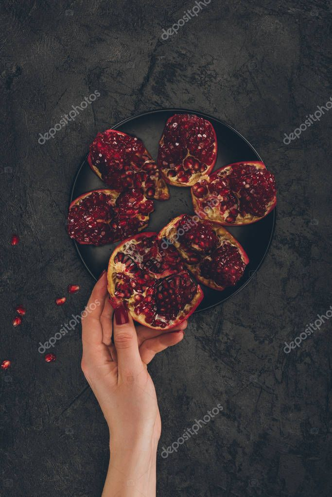 woman taking piece of pomegranate