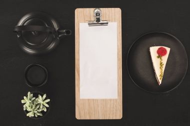 sheet of paper on clipboard and tea set