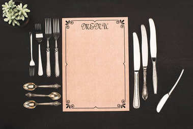 Top view of decorative blank menu and cutlery on black stock vector