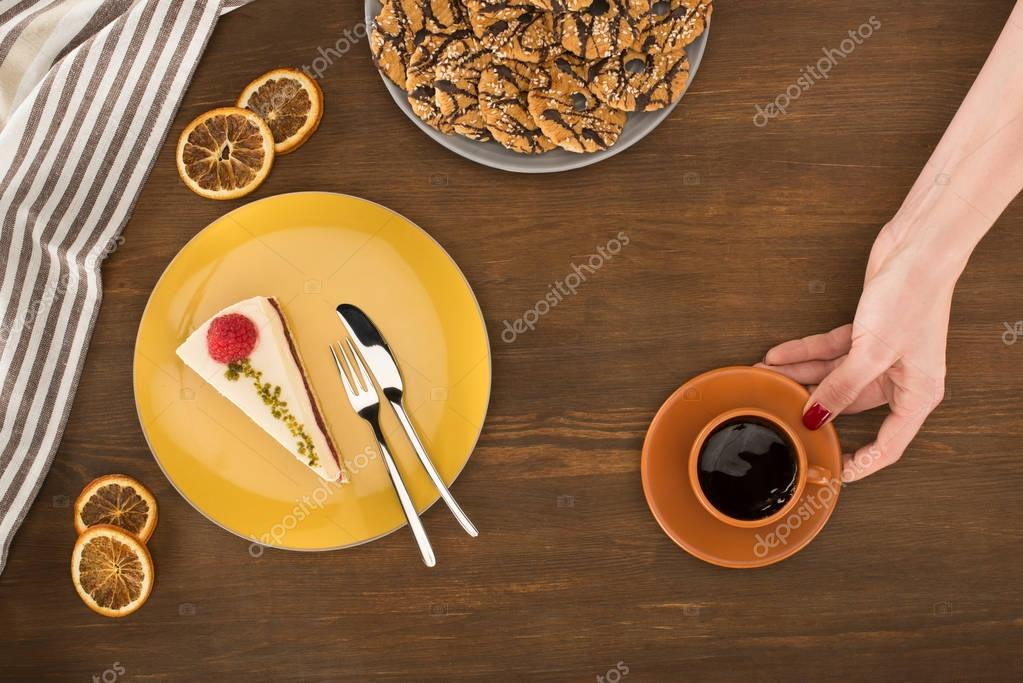 hand with coffee and dessert