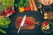 Fotografie Tomaten mit Messer auf Schneidebrett