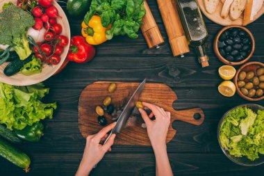 hands slicing olives