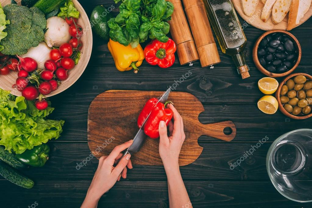 hands slicing pepper by knife