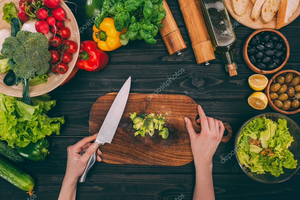 hands slicing broccoli
