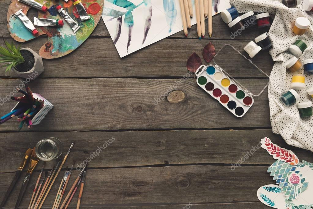 wooden table with paints and sketches