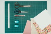 Photo Top view of sheets of paper and scissors with stationery knife for making scrapbooking postcard