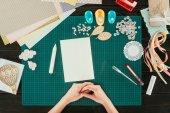 Fotografia immagine potata del progettista che si siede al tavolo con foglio di carta bianco vuoto