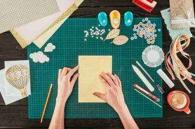 cropped image of designer sitting at working table with template for scrapbooking postcard