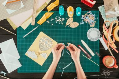 cropped image of designer making bow with ribbon