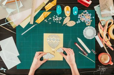 cropped image of designer adding clouds to scrapbooking handmade postcard
