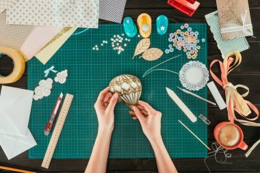 cropped image of designer making scrapbooking decoration for postcard in shape of balloon