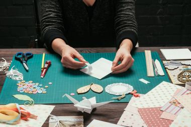cropped image of woman making scrapbooking postcard