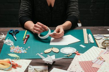 cropped image of designer taking piece of adhesive tape