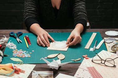 cropped image of woman making scrapbooking handmade postcard