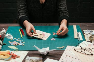 cropped image of woman adding bow to handmade scrapbooking postcard