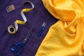 Fotografia vista superiore di forbici, nastro adesivo e scatola con perni di misurazione sopra tessuto viola