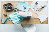 pohled shora švadlena pracoviště s látky, šicí stroje, koncepty a stitchings