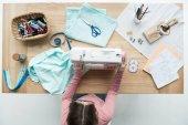 Fotografia vista superiore di sarta donna sul posto di lavoro con macchina da cucire