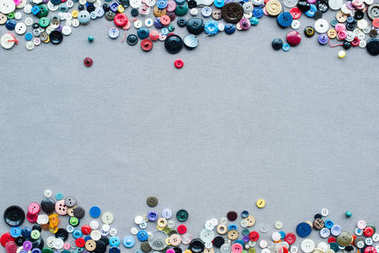 top view of colorful buttons frame on grey cloth background