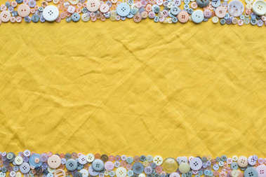 Top view of colorful buttons frame on yellow cloth background with copy space stock vector